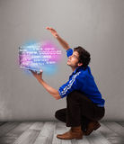 Casual man holding laptop with exploding data and numbers Stock Photo