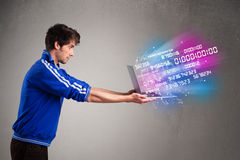 Casual man holding laptop with exploding data and numbers Stock Image