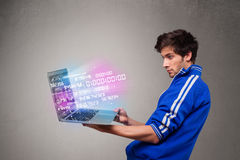 Casual man holding laptop with exploding data Royalty Free Stock Images