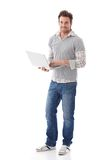 Casual man holding laptop smiling Royalty Free Stock Images