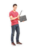 Casual man holding an open movie clap. Full length portrait of a casual man holding an open movie clap isolated on white background Stock Photo