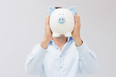 Casual man holding piggy bank in front of his face Royalty Free Stock Photos