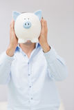 Casual man holding piggy bank in front of his face Royalty Free Stock Images