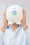 Casual man holding piggy bank in front of his face Stock Photos