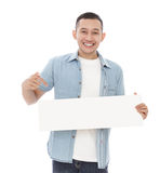 Casual man holding and pointing blank white board Stock Photos