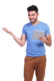 Casual man holding a tablet pad is inviting you Stock Images