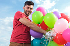 Casual man holds a lot of baloons Stock Photography