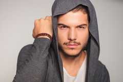 Casual man with hoodie on holds hand near head Stock Photos