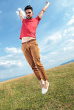 Casual man jumps with hands in air Stock Photos