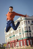 Casual man jumps hight in air on sidewalk in  old city and looki Royalty Free Stock Photos