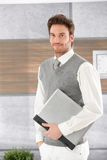 Casual man with laptop smiling Royalty Free Stock Photos