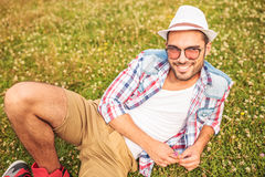 Casual man laying down on a grass field. And smiles to the camera Stock Image