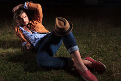 Casual man laying down with hat on knee Royalty Free Stock Image