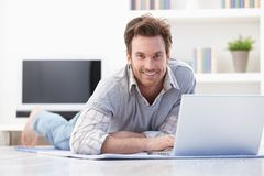 Casual man laying on floor at home smiling Stock Image