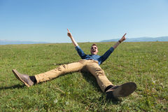Casual man laying in the grass and cheering. Casual young man laying in the grass on a field and cheering with hands in air while screaming and looking at the Royalty Free Stock Photos