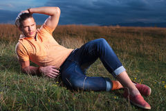 Casual man laying in the grass and fixing his hair Stock Photo