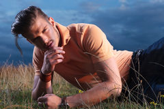 Casual man laying in grass with hand at chin Stock Images