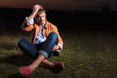 Casual man laying in the grass and holding his hat Royalty Free Stock Image