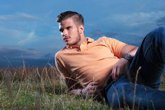 Casual man laying in the grass and looking away Stock Images