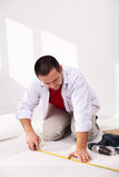 Casual man laying isolation beneath flooring. Installing laminate flooring - laying the isolation foam layer Royalty Free Stock Photo
