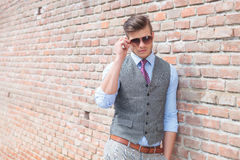 Casual man leans on wall and adjust sunglasses Royalty Free Stock Photos