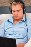Casual man listening music. With headphones at home stock images
