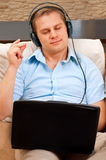 Casual man listening music with headphones. At home stock images