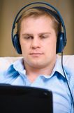 Casual man listening music with headphones. At home royalty free stock photo