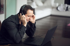 Casual man listening music by headphones and laptop Royalty Free Stock Photography