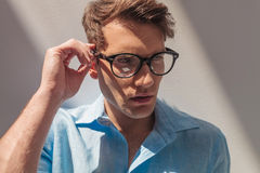 Casual man looking away while fixing his glasses. Royalty Free Stock Photos