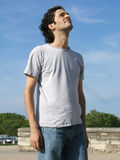 Casual man looking up. Casual man with long hairs and t-shirt looking up royalty free stock image