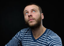 Casual man looking up over black background. Portrait of casual man looking up over black background Royalty Free Stock Photo