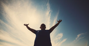 Casual man looking very happy with his arms up. Against blue sky in backlight . Young casual man gesturing success Royalty Free Stock Image