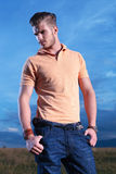 Casual man looks away with both thumbs in pockets Royalty Free Stock Photography
