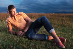 Casual man looks away while laying in grass Stock Images