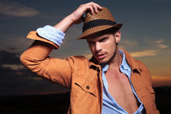 Casual man looks away with straw in mouth and hand on hat Royalty Free Stock Image