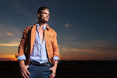 Casual man looks away with thumbs in pockets at sunset Stock Image