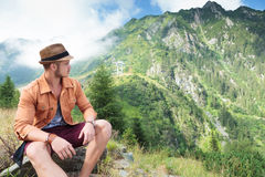 Casual man looks back at mountain Stock Photo