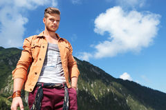 Casual man looks down at camera in mountains Royalty Free Stock Photos