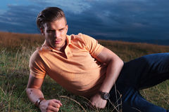 Casual man looks frowned at you, while laying in grass Stock Photography