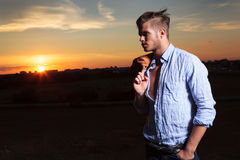 Casual man looks to his side with sunset behind Stock Photography
