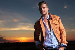 Casual man looks up with hands in pockets at sunset Royalty Free Stock Photo