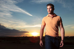 Casual man looks up with the sunset behind Stock Photo