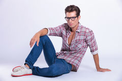 Casual man looks at you from the floor royalty free stock photography