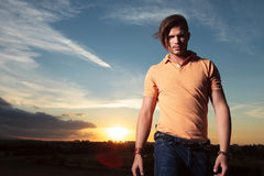 Casual man looks at you with sunset behind Stock Photography