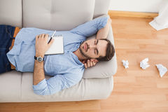 Casual man lying on couch with crumpled papers Royalty Free Stock Photo
