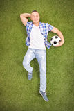 Casual man lying on a field and holding football. Vertical shot of a casual young man lying on a grass field, holding a football and looking at the camera Stock Images