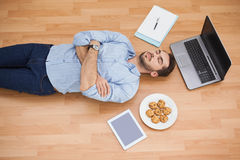 Casual man lying on floor surrounded by his possesions Stock Photography