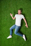 Casual man lying in funny position on the grass Royalty Free Stock Photography