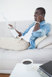 Casual man lying on sofa on the phone holding newspaper Royalty Free Stock Photos